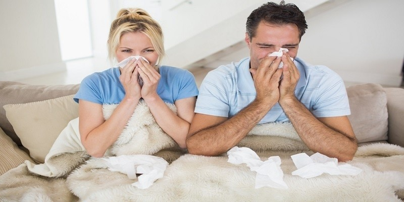 Couple suffering from cold as they sit on bed at home