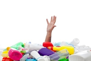 Environment concept with human hand reaching out from beneath plastic recipients