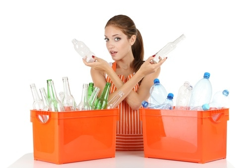 Young girl sorting glass and plastic bottles isolated on white