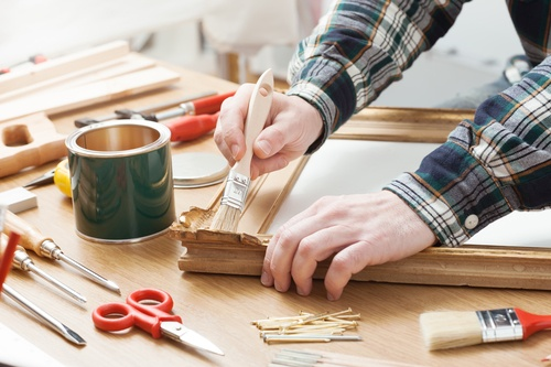Man varnishing a wooden frame at home