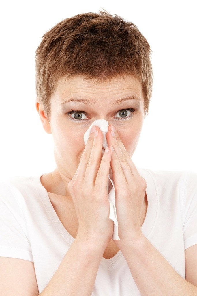Woman in short hair blowing her nose on the tissue on white background