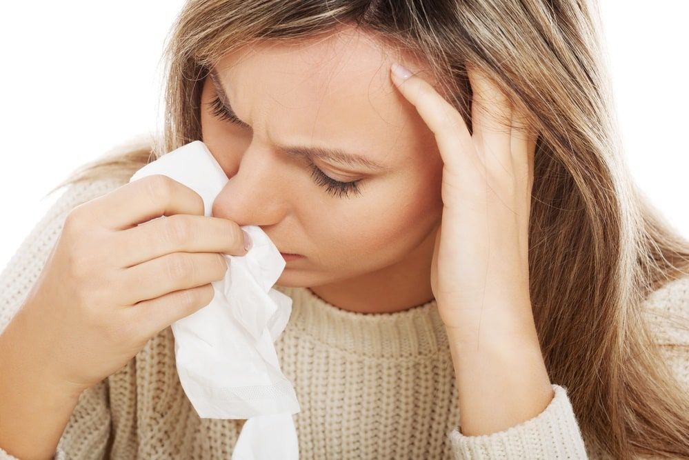 Young woman with tissues crying/ having runny nose.
