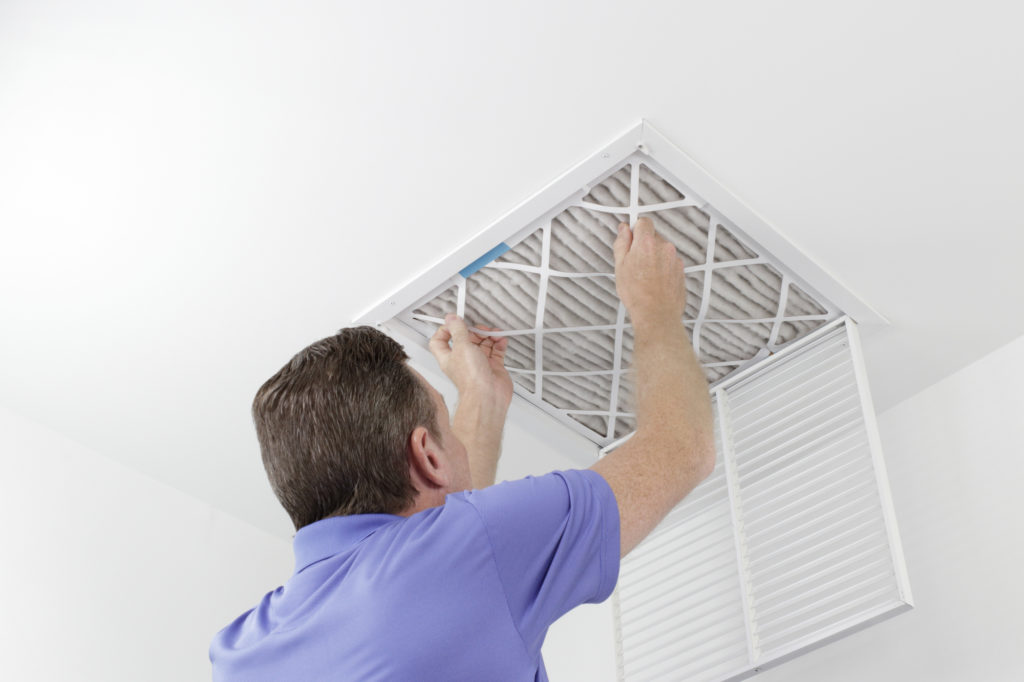 Caucasian male removing a square pleated dirty air filter with both hands from a ceiling air duct. Guy taking out an unclean air filter from a home ceiling air vent.