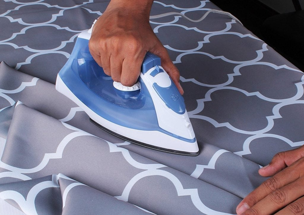 Man ironing a gray fabric