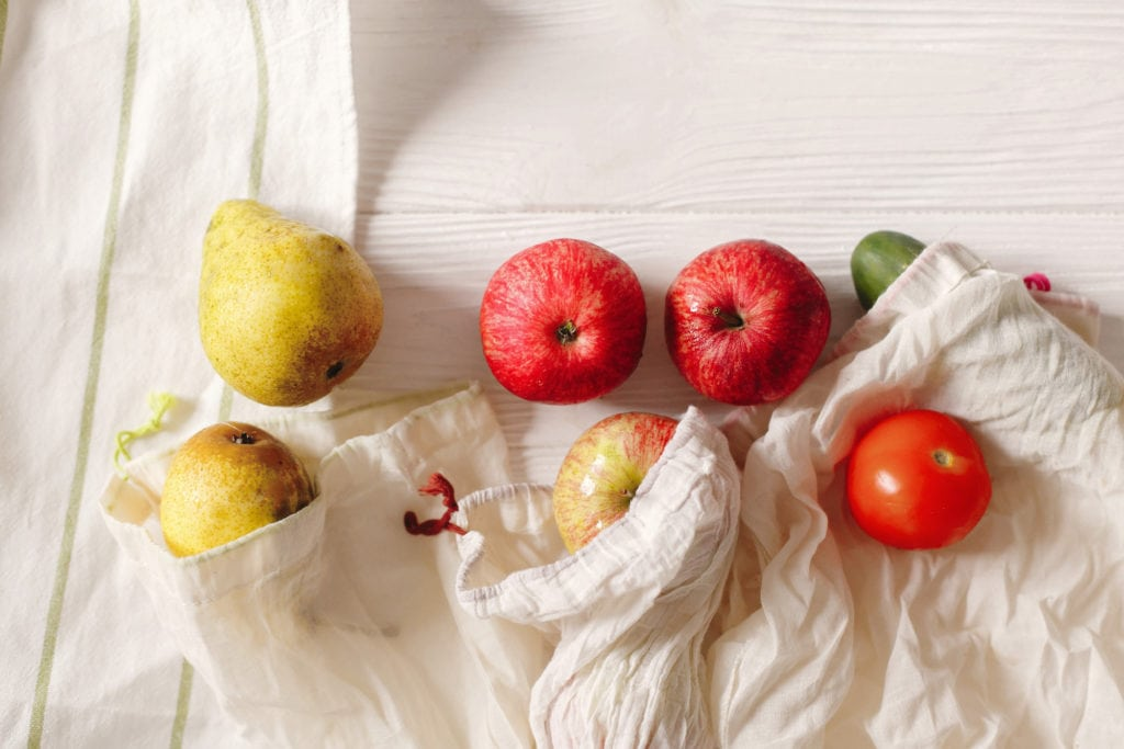 zero waste food shopping. eco natural bags with fruits, eco friendly, flat lay. sustainable lifestyle concept. plastic free items. reuse, reduce, recycle, refuse. groceries in eco bags