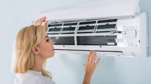 Woman with short, blond hair looking at the aircon filter