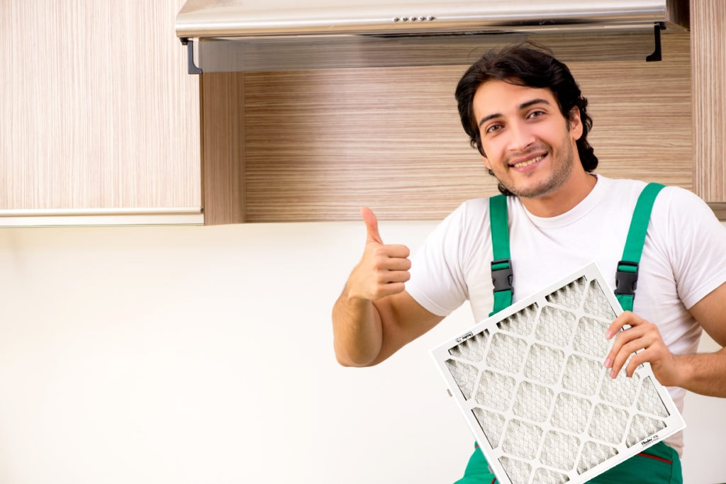 Handyman holding a furnace filter with thumbs up