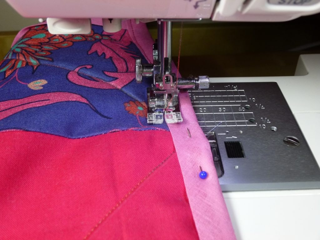 Sewing a pink cloth with pins on the side