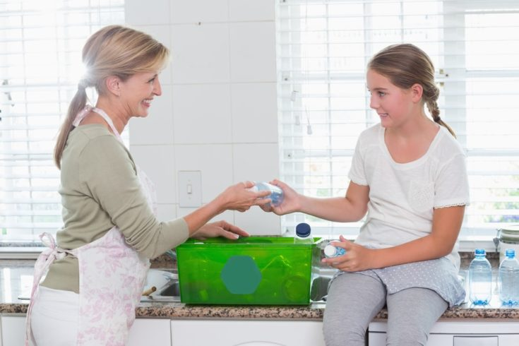 Mother and daughter putting bottles in recycling box at home in the kitchen