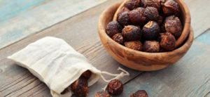 soap nuts in cloth bag and in the wooden bowl in wooden background
