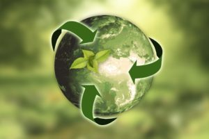 Earth with recycling arrows symbol in green background