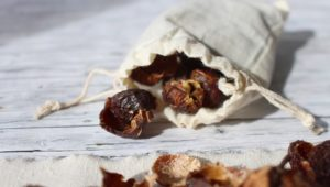 Soap nuts in cloth bag in wooden background