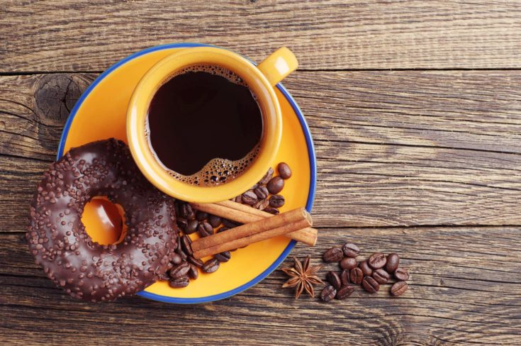 Chocolate donut and cup of hot coffee on vintage wooden table. Top view